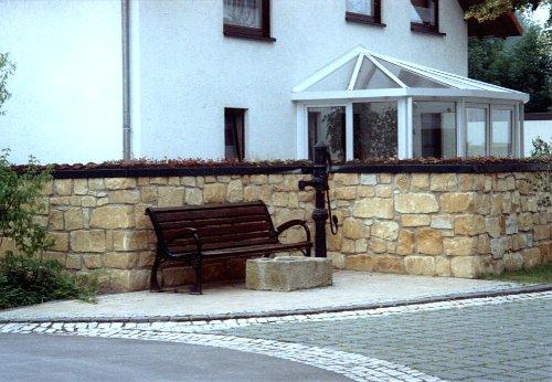 Sandsteinmauer mit Begrünung.